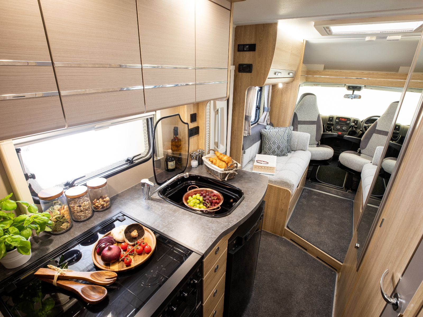 Kitchen layout with prepared food and a view of the lounge and driving area