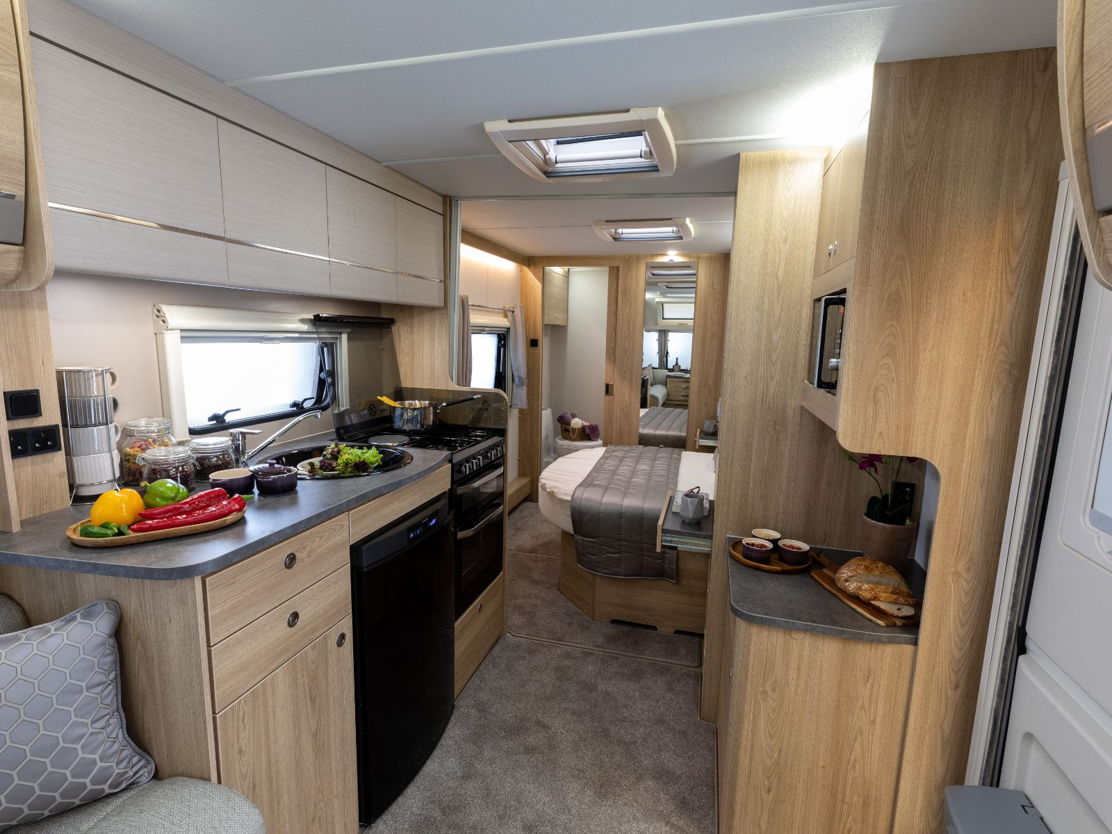Kitchen layout with overhead storage, fridge and oven with food resting on the counter and a view of the bedroom with double bed'