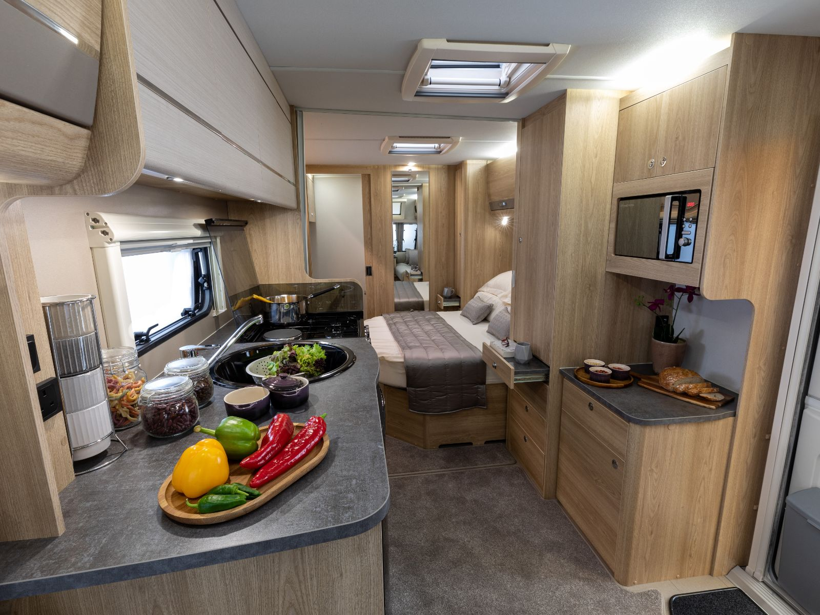 Kitchen layout with overhead storage, microwave and oven with food resting on the counter and a view of the bedroom with double bed'