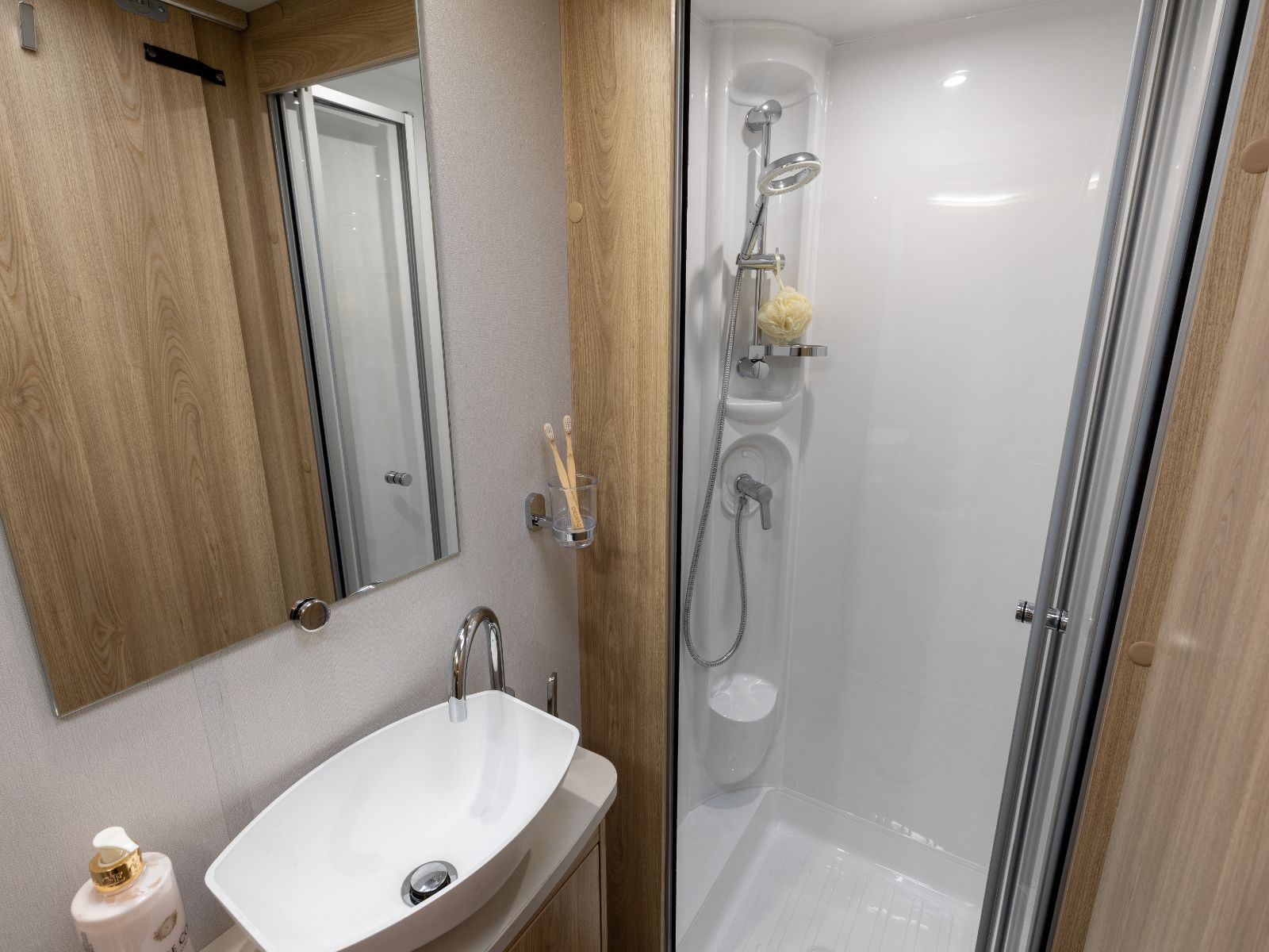Bathroom layout with shower and sink with mirror above'