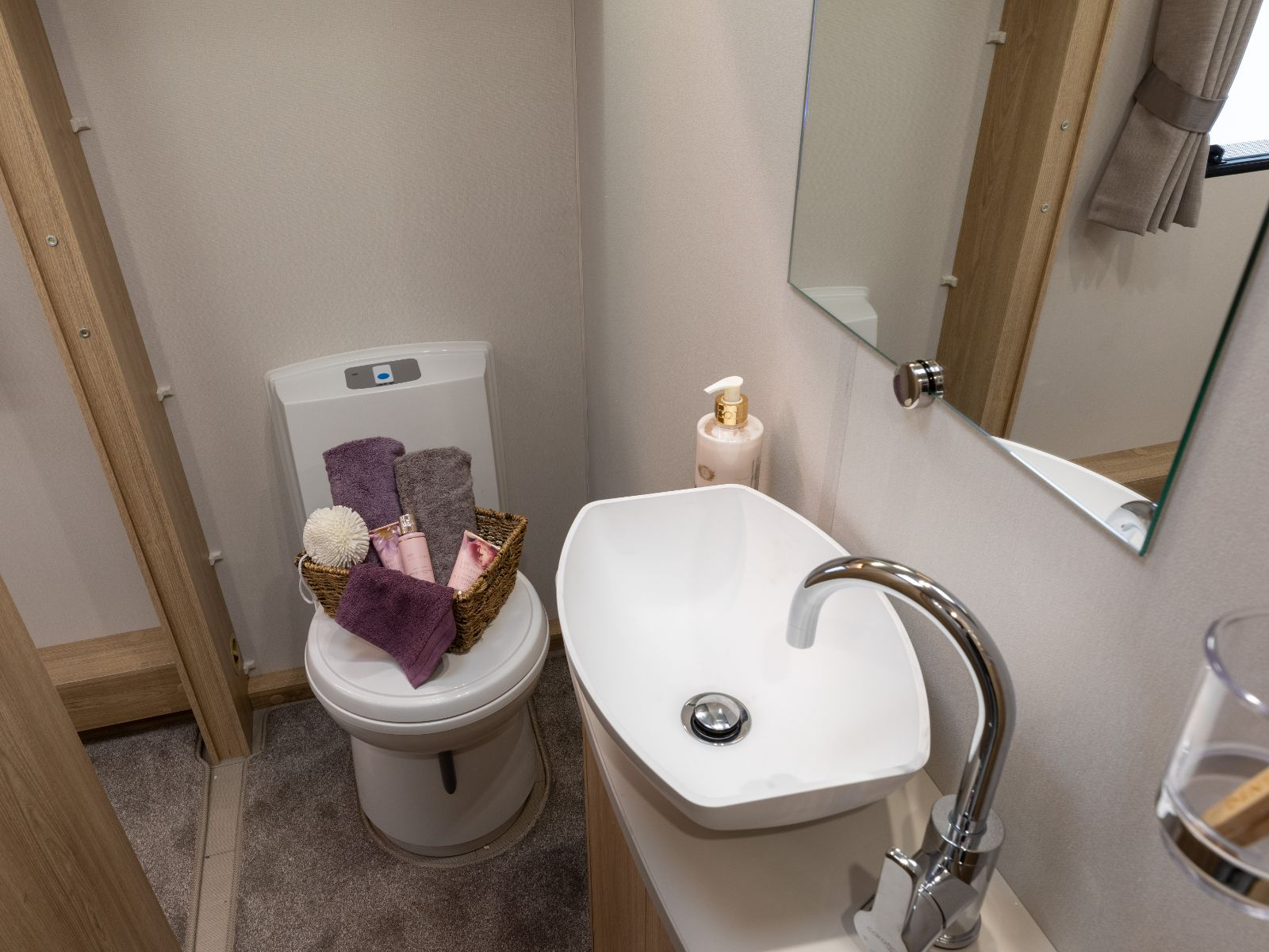 Bathroom layout with sink and toilet with assortment of toiletries'