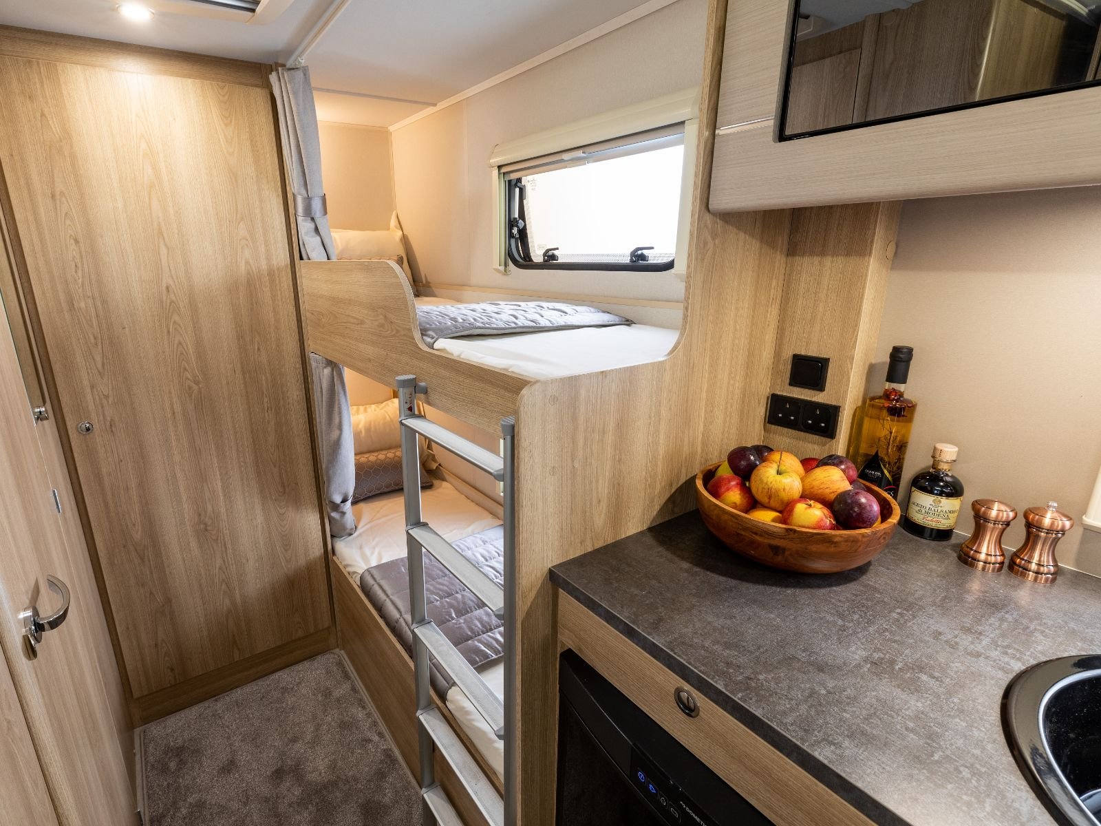 Double bunk bed layout with ladder access and kitchen view'