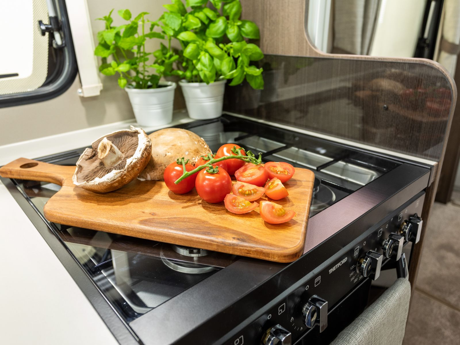 Mushrooms and tomatoes resting on wooden chopping board on top of the oven glass protector'