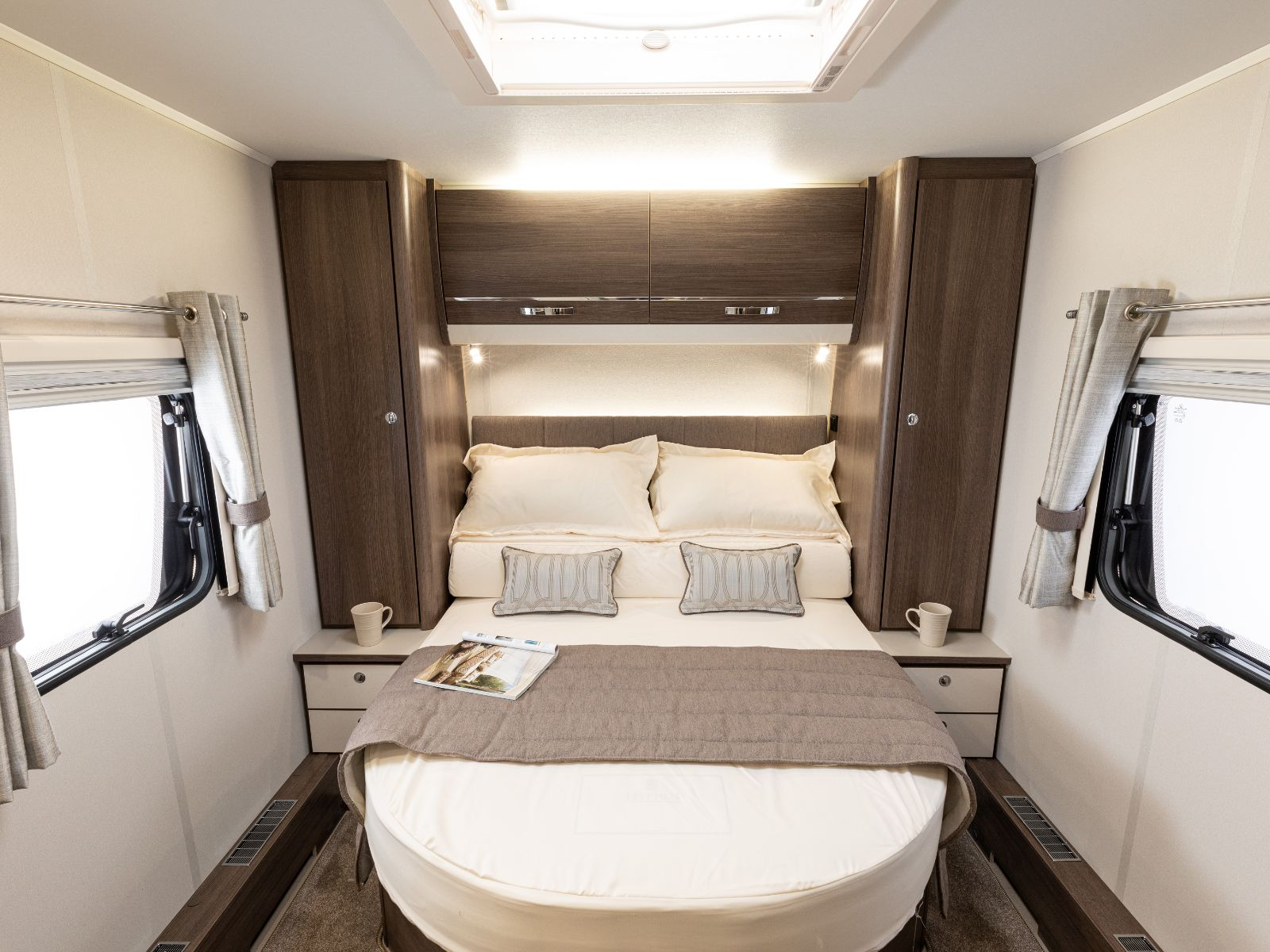 Bedroom layout featuring a double bed, overhead storage and windows either side'