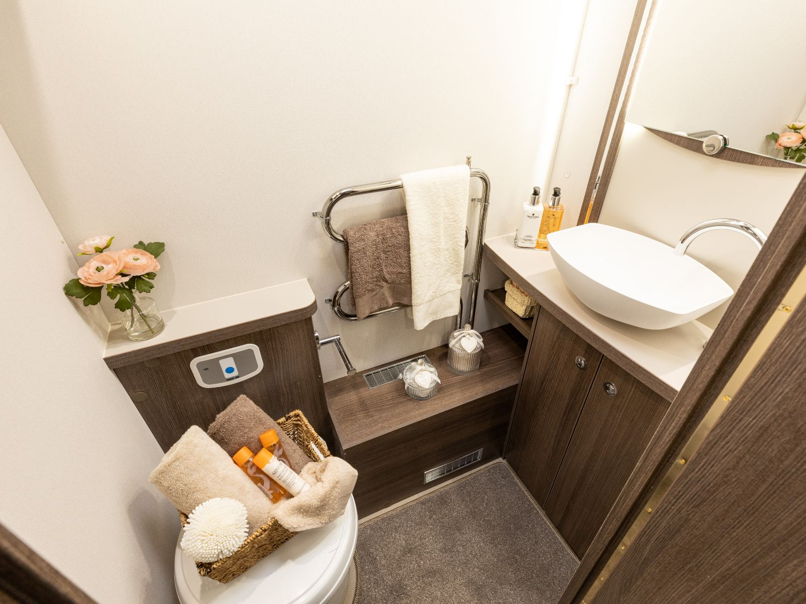 Bathroom layout with sink and toilet with an assortment of toiletries'