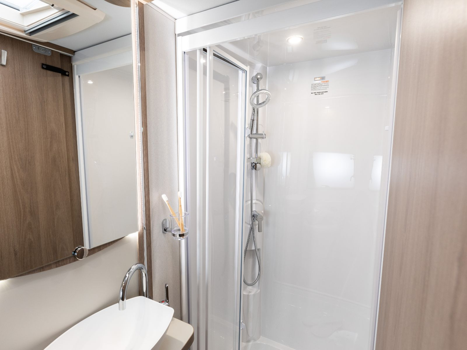 Bathroom layout with walk in shower, sink and mirror'