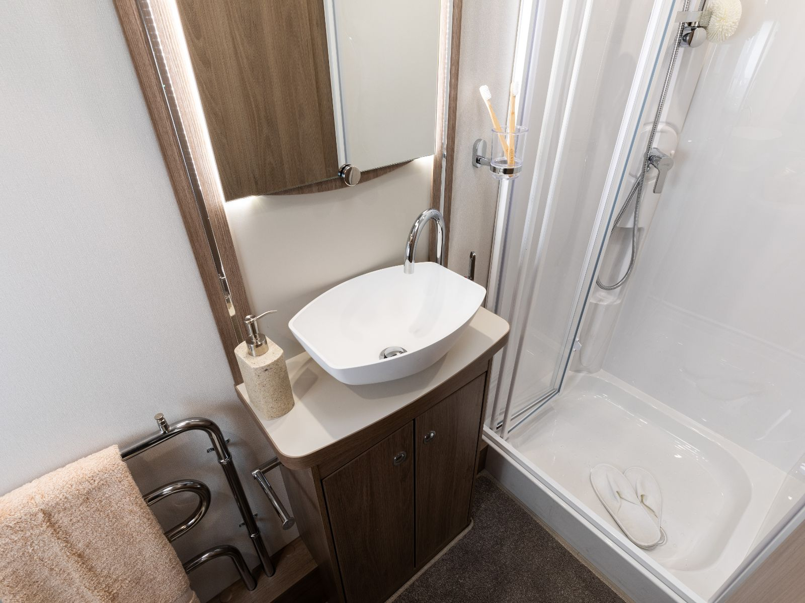 Bathroom sink with walk in shower to the right, mirror above and heated towel rack to the left'