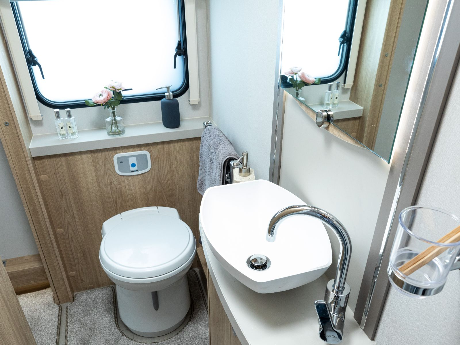 Bathroom layout with sink, mirror, window and toilet'