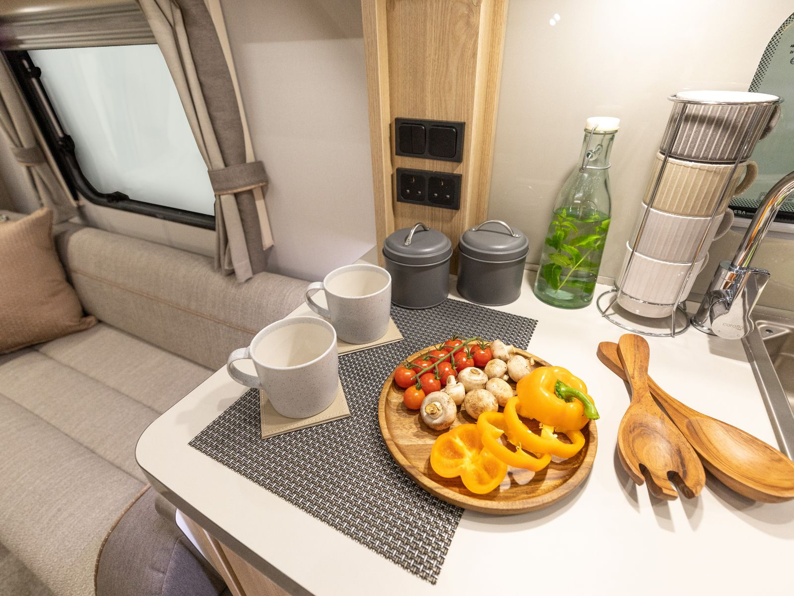 Food resting on kitchen counter with wooden utensils and coffee cups'