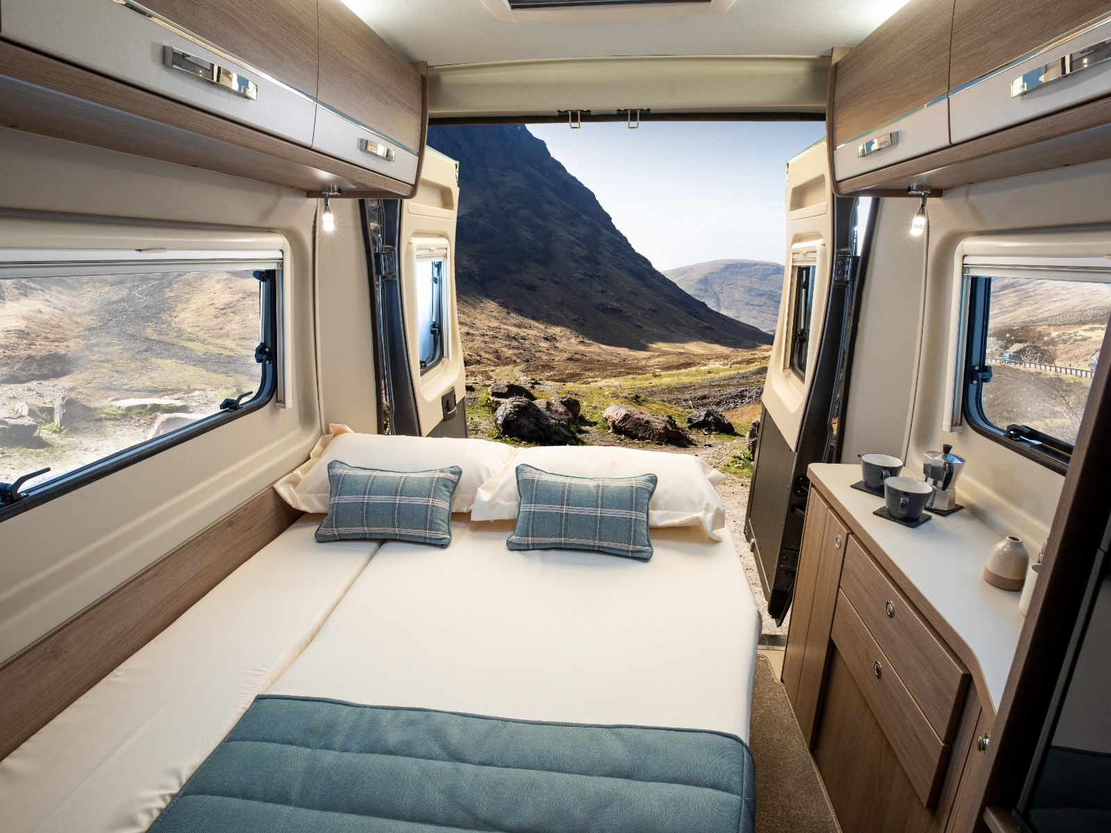 Bedroom layout with backdoors open revealing a mountain backdrop