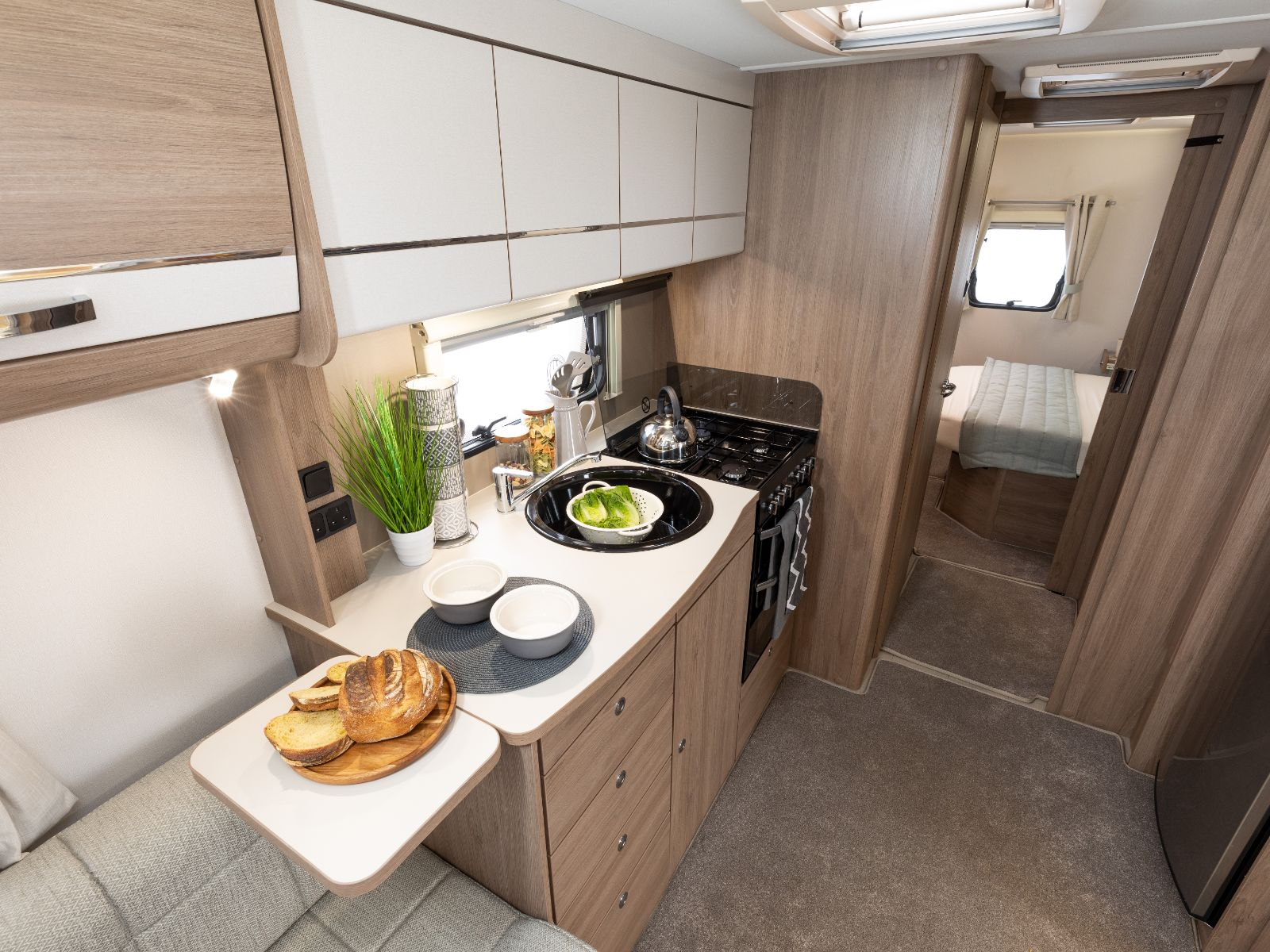 Kitchen layout with overhead storage, oven and bread resting on counter with a view of the bedroom featuring a double bed'