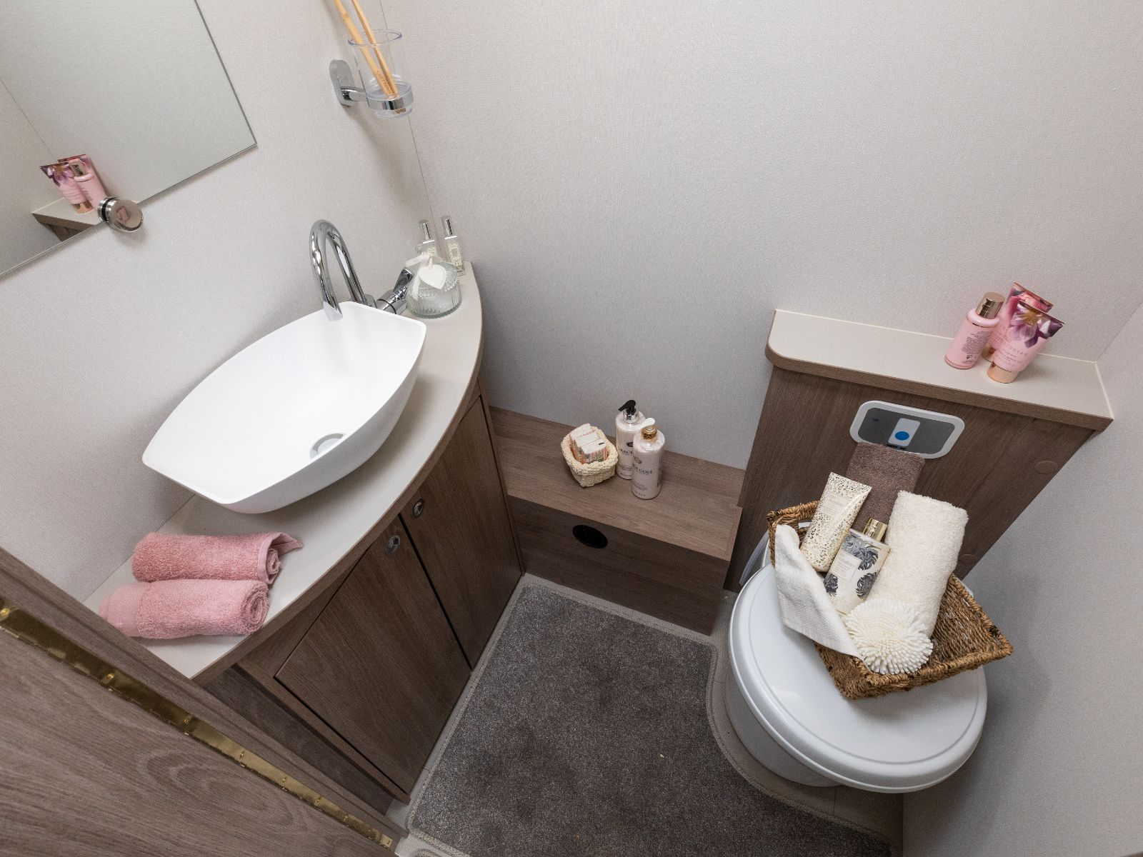 Bathroom layout with sink, mirror and toilet with assortment of toiletries on top'