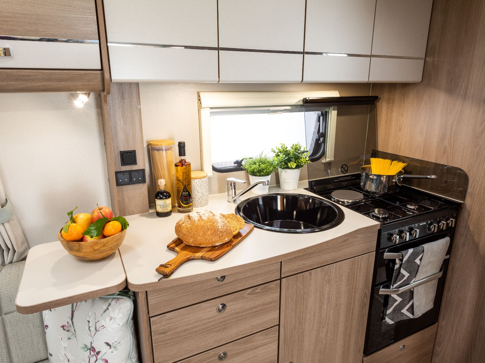 Kitchen layout with overhead storage, sink and oven with bowl of oranges and bread resting on counter'