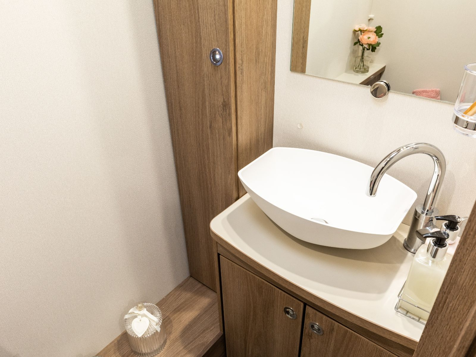 Bathroom sink with mirror above and toiletries storage on the left hand side'