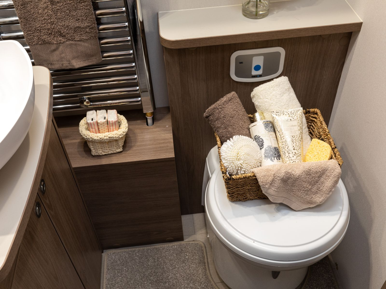 Bathroom layout with heated towel rack and toilet with assortment of toiletries'