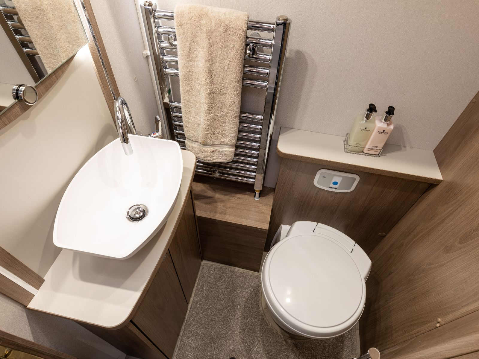 Bathroom layout with sink, mirror, heated towel rack and toilet'