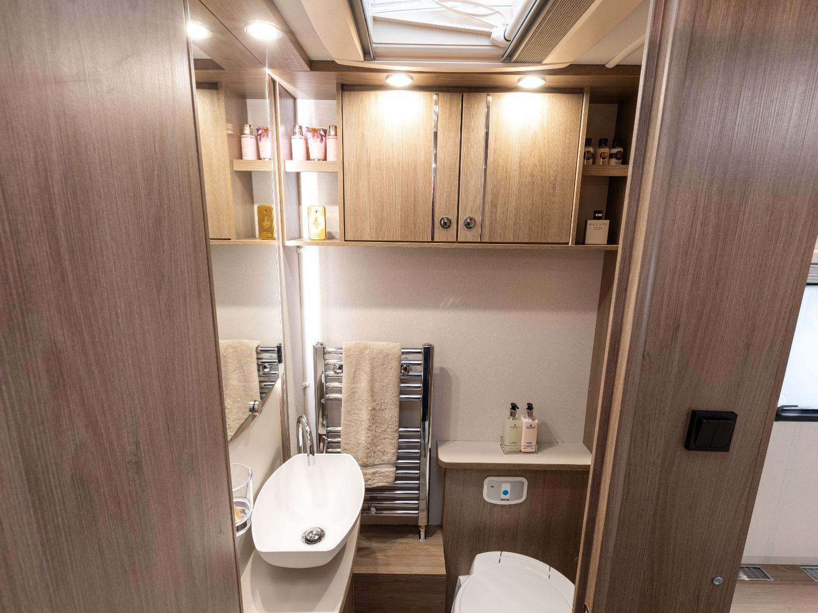 Bathroom layout with mirror, sink, heated towel rack, toilet and toiletry storage'