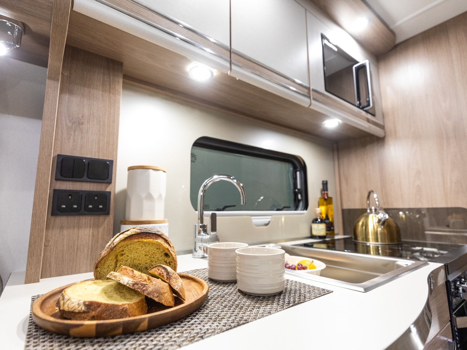 Bread resting on counter and view of overhead storage and microwave in kitchen'