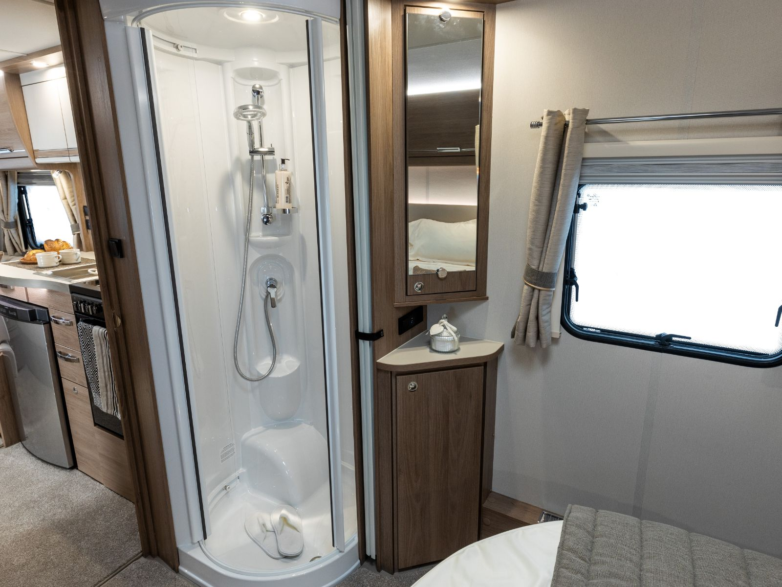 En-suite shower in bedroom with mirror, storage and window on right hand side with view of the kitchen'
