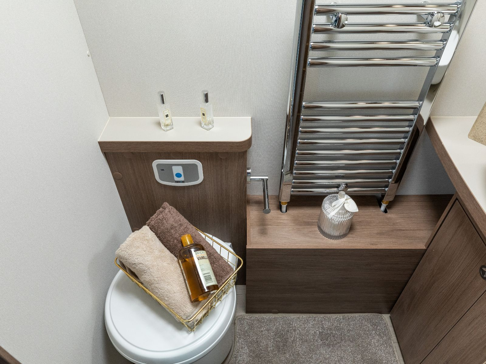 Heated towel rack and toilet with assortment of toiletries on top'