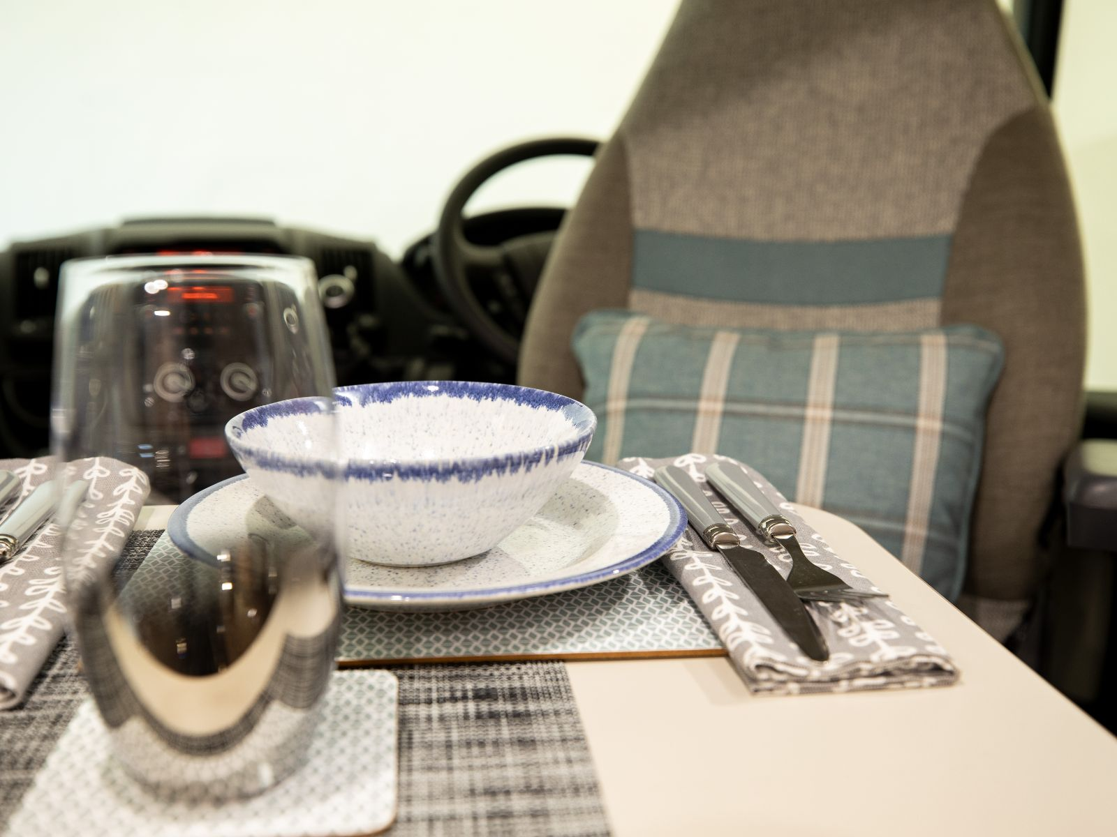 Glass and bowl set up on the dinette in front of the drivers seat'