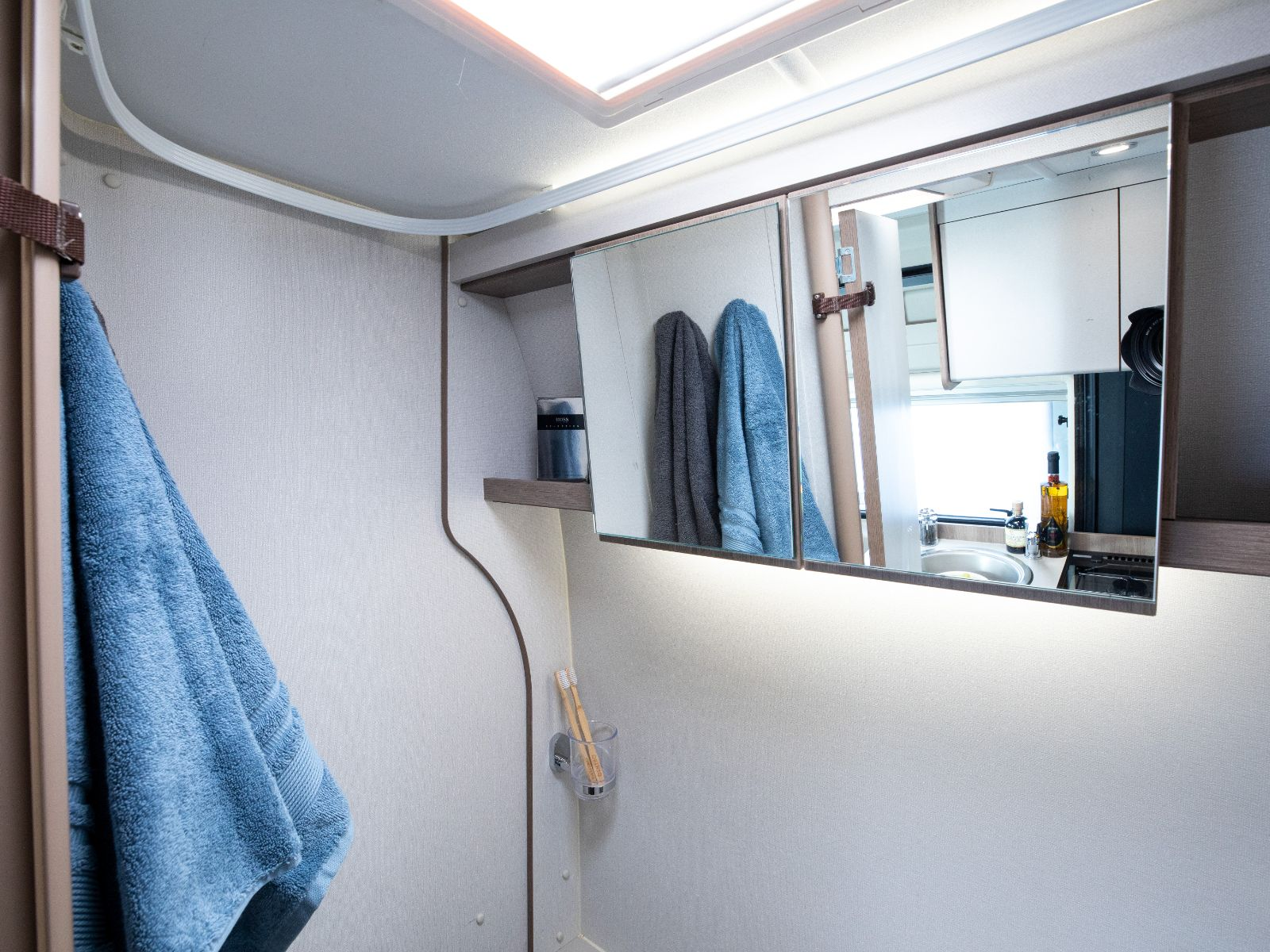 Bathroom mirrors with towels in reflection and toiletries stored next to them'