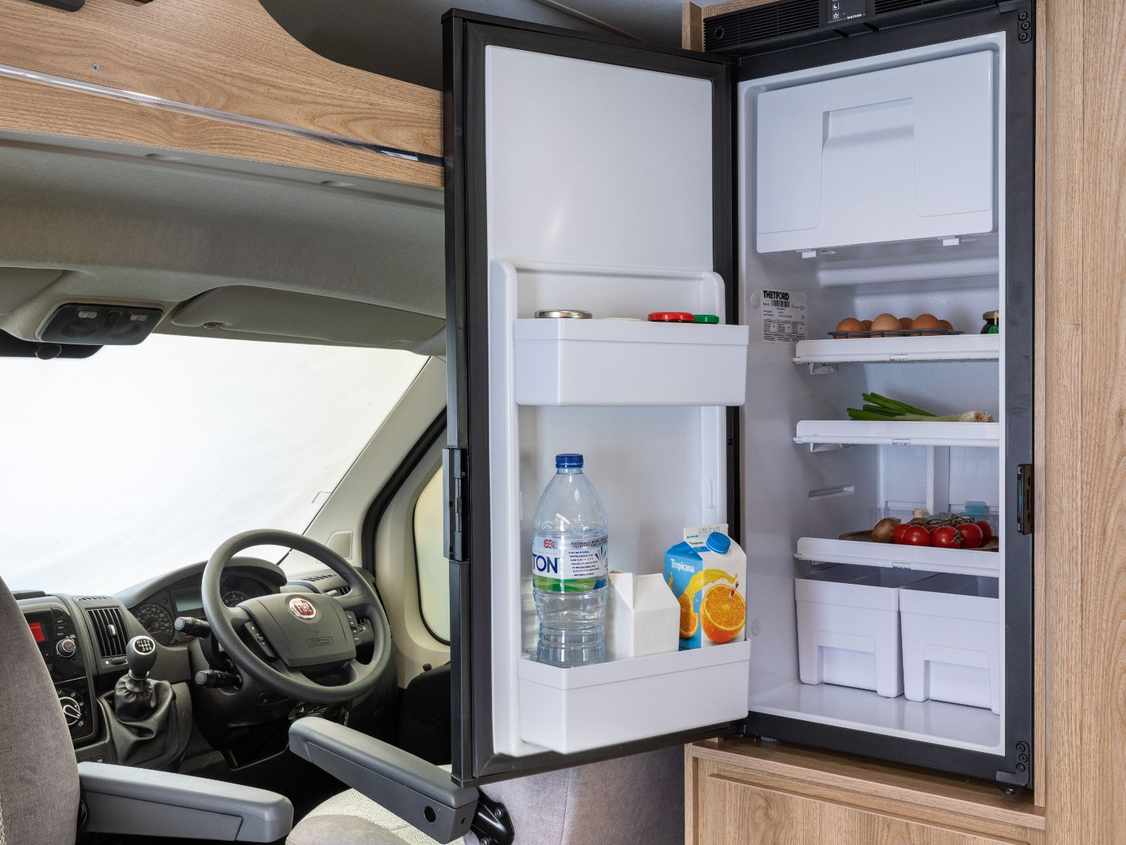 Open fridge with steering wheel in background'