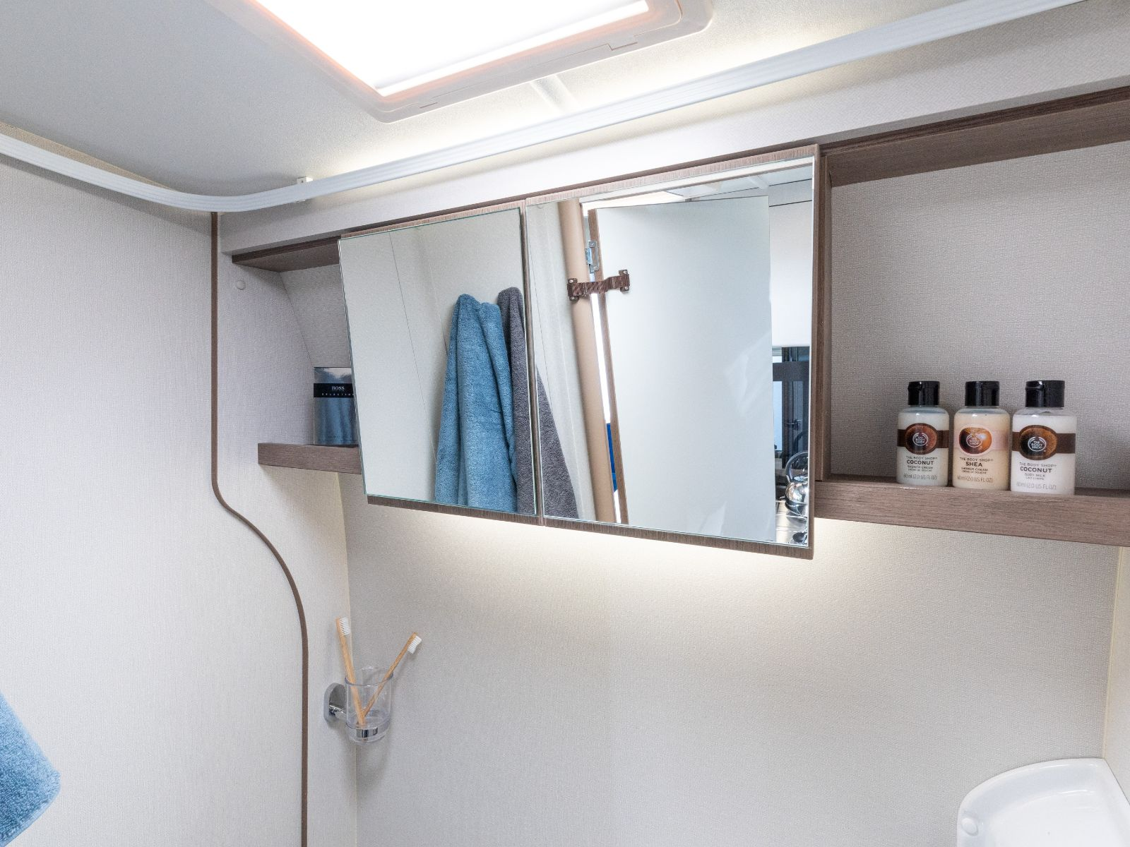 Bathroom mirrors with towels and assortment of toiletries'