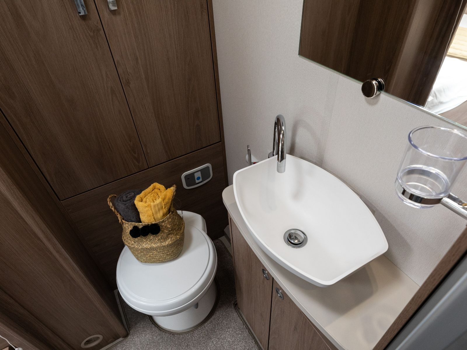 Bathroom toilet and sink with toiletries and storage'