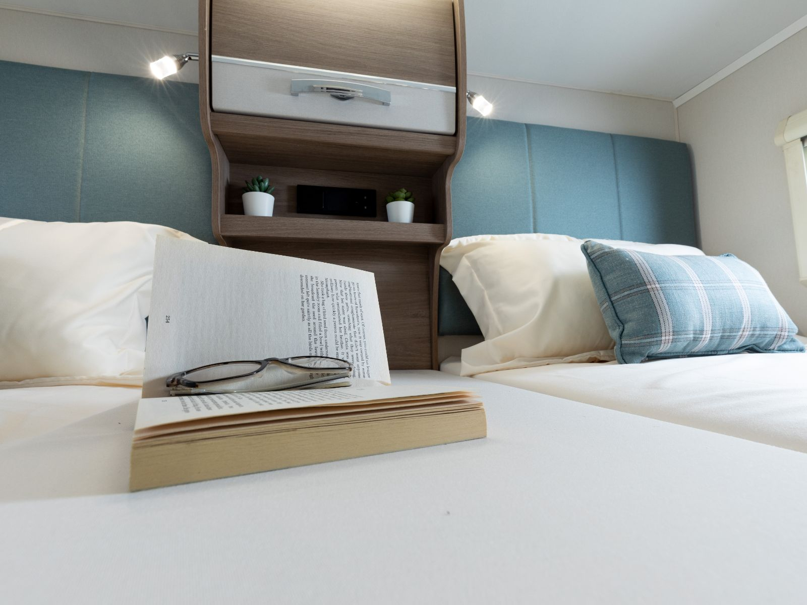 Book and glasses on one of the single beds decorated with pillows'