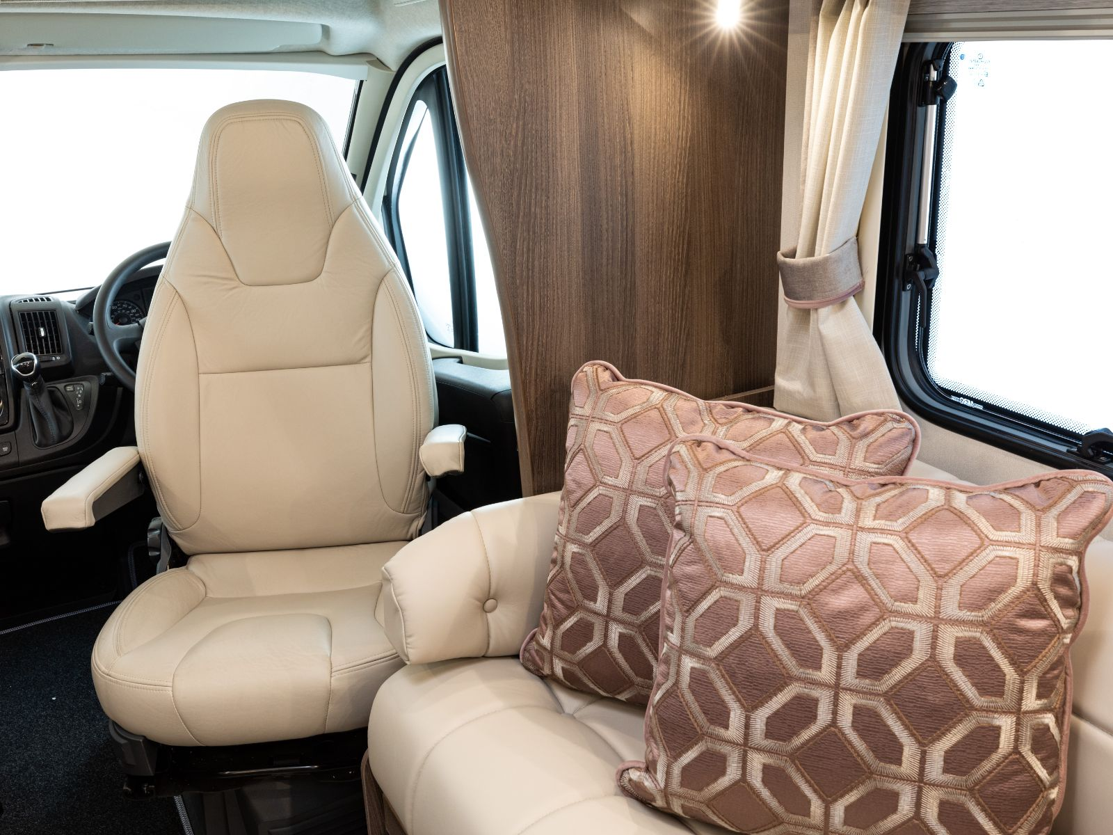 Sofa decorated with cushions and drivers seat behind'