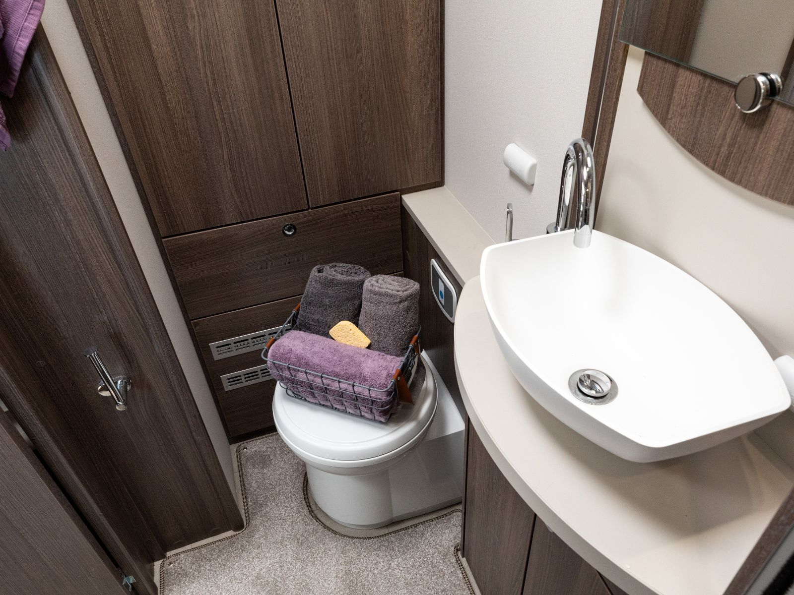 Bathroom layout with sink and toilet featuring assortment of toiletries'