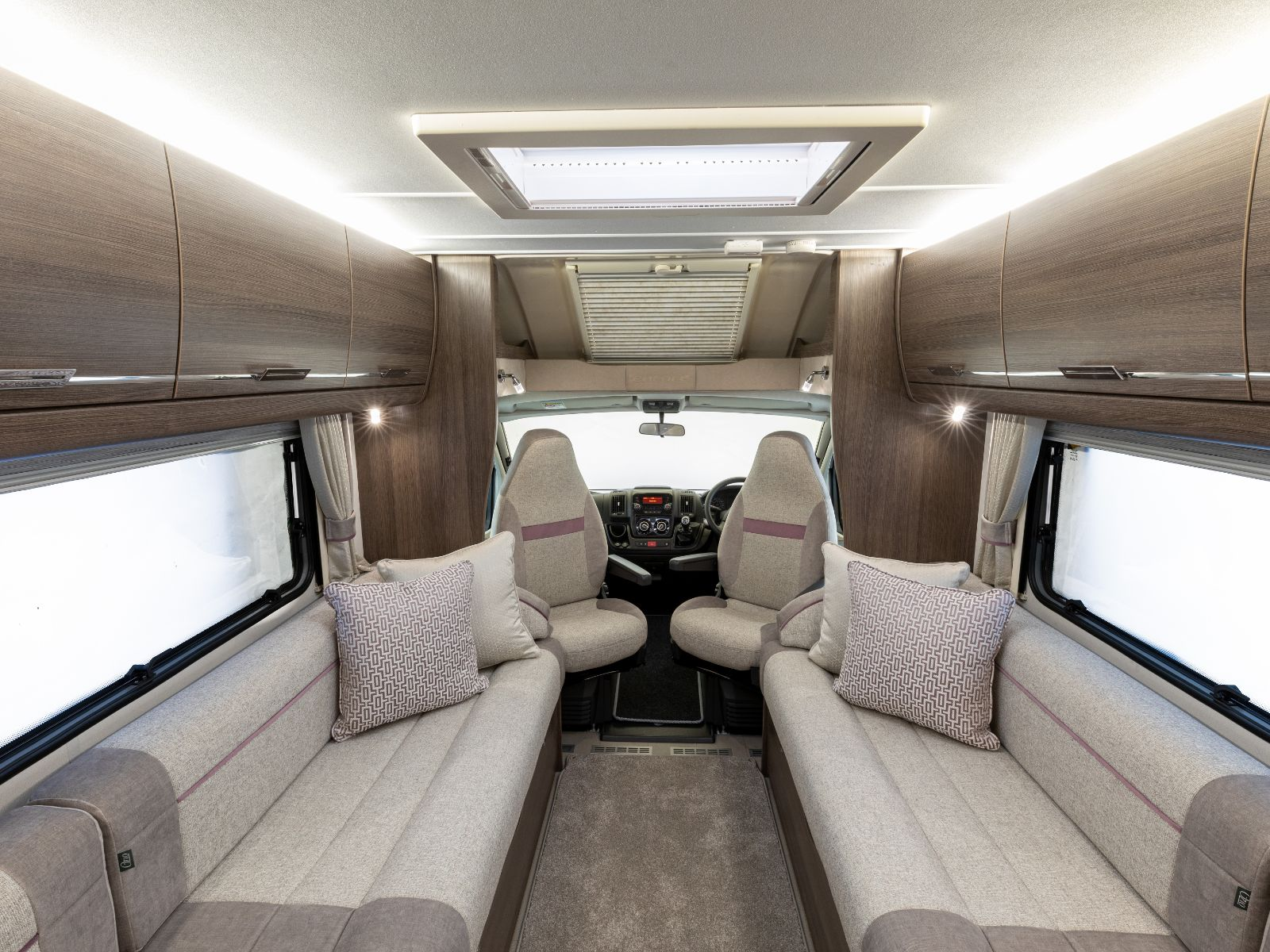 Lounge layout with two sofas decorated with cushions and overhead storage with view of driving area'