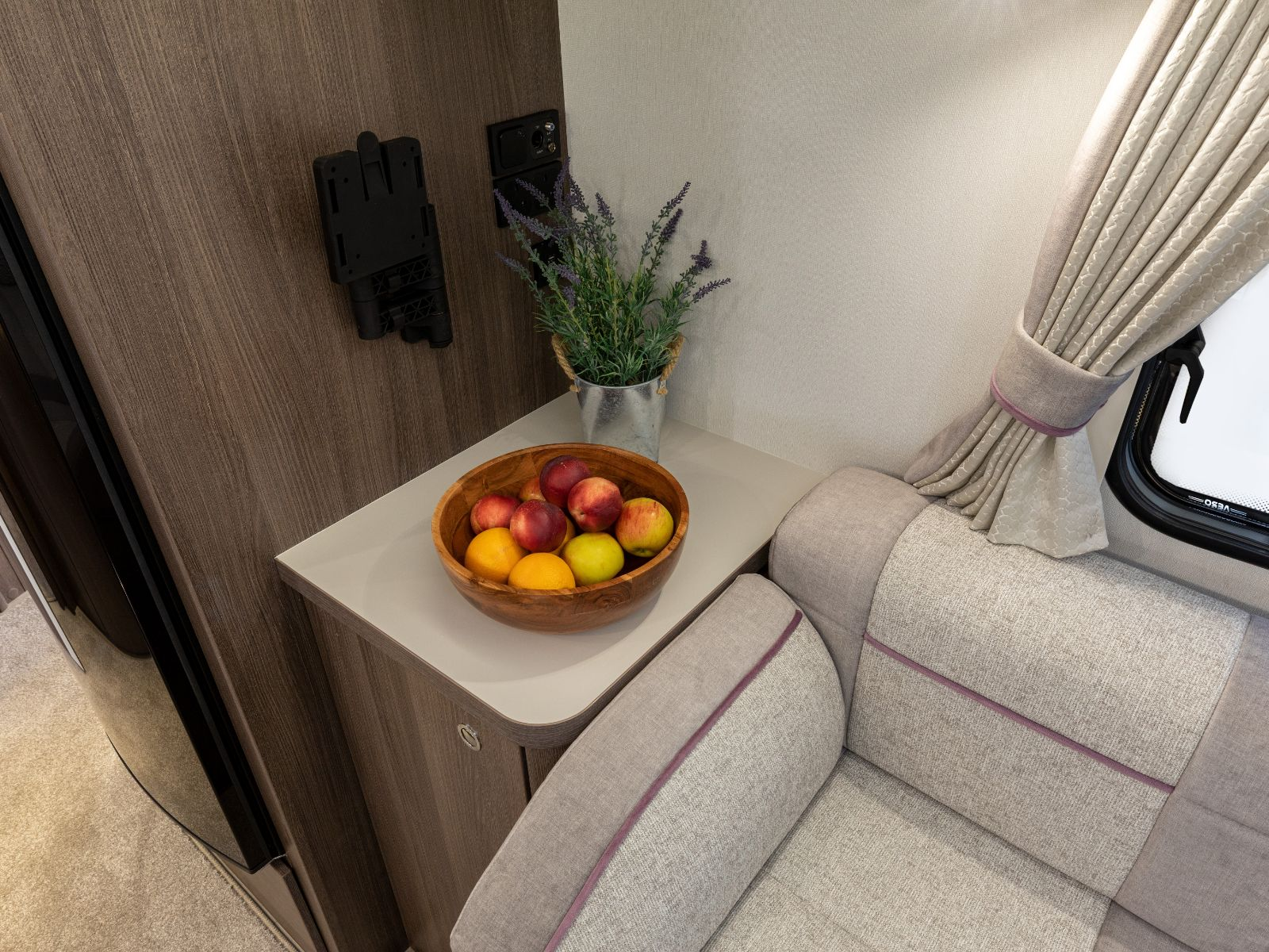 Fruit bowl and lavender plant on side table'
