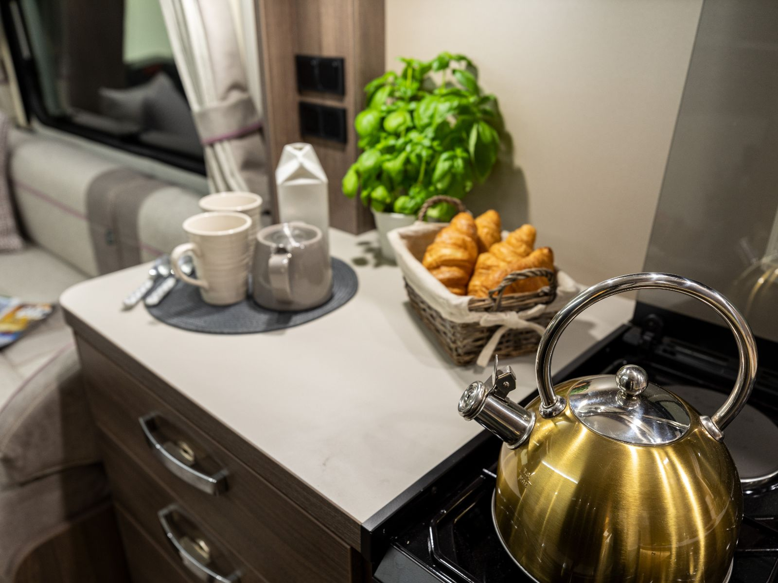 Kettle on stove top with assortment of food and cups on counter top'