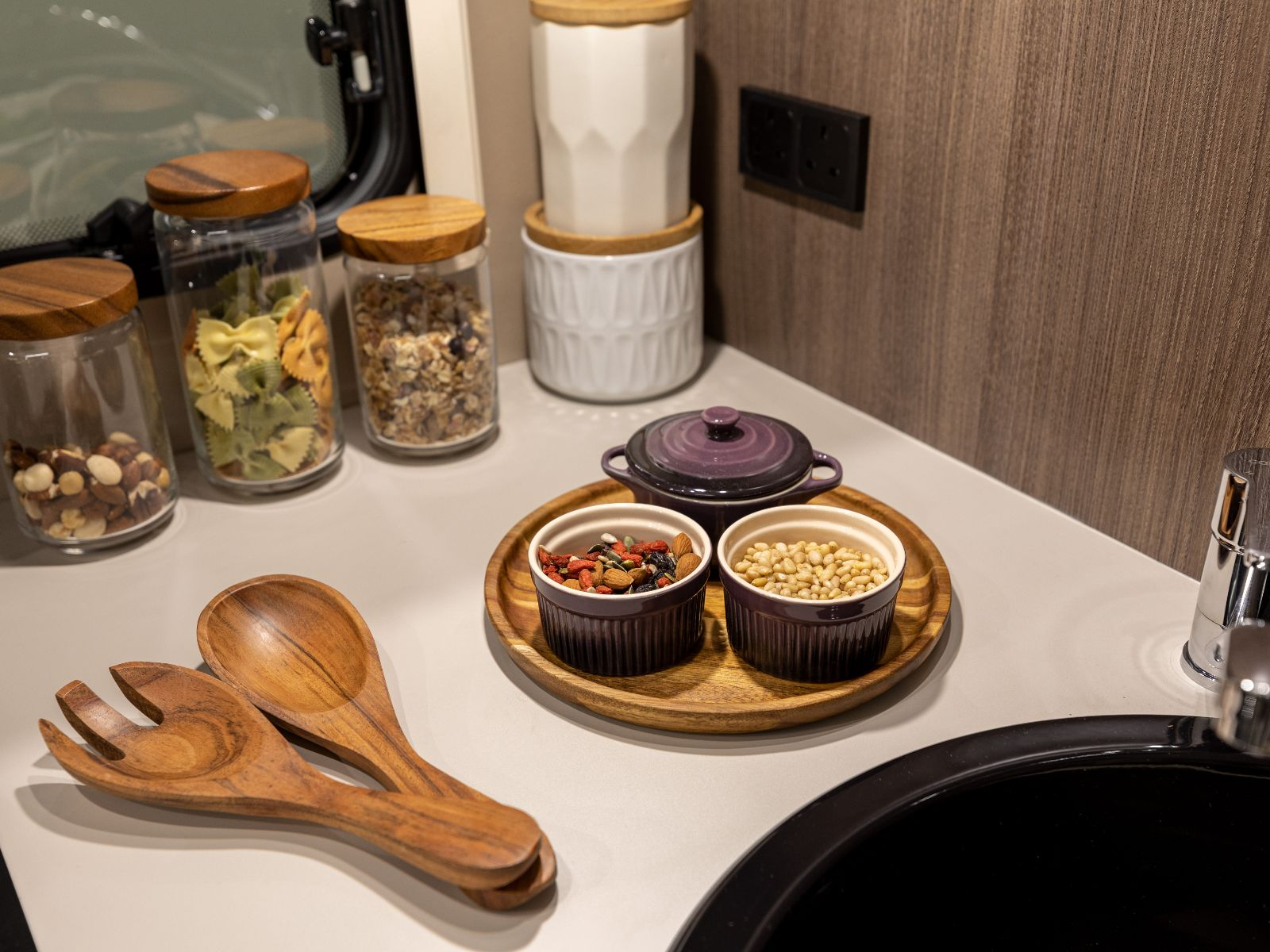 Assortment of food, containers and wooden utensils on kitchen counter top'