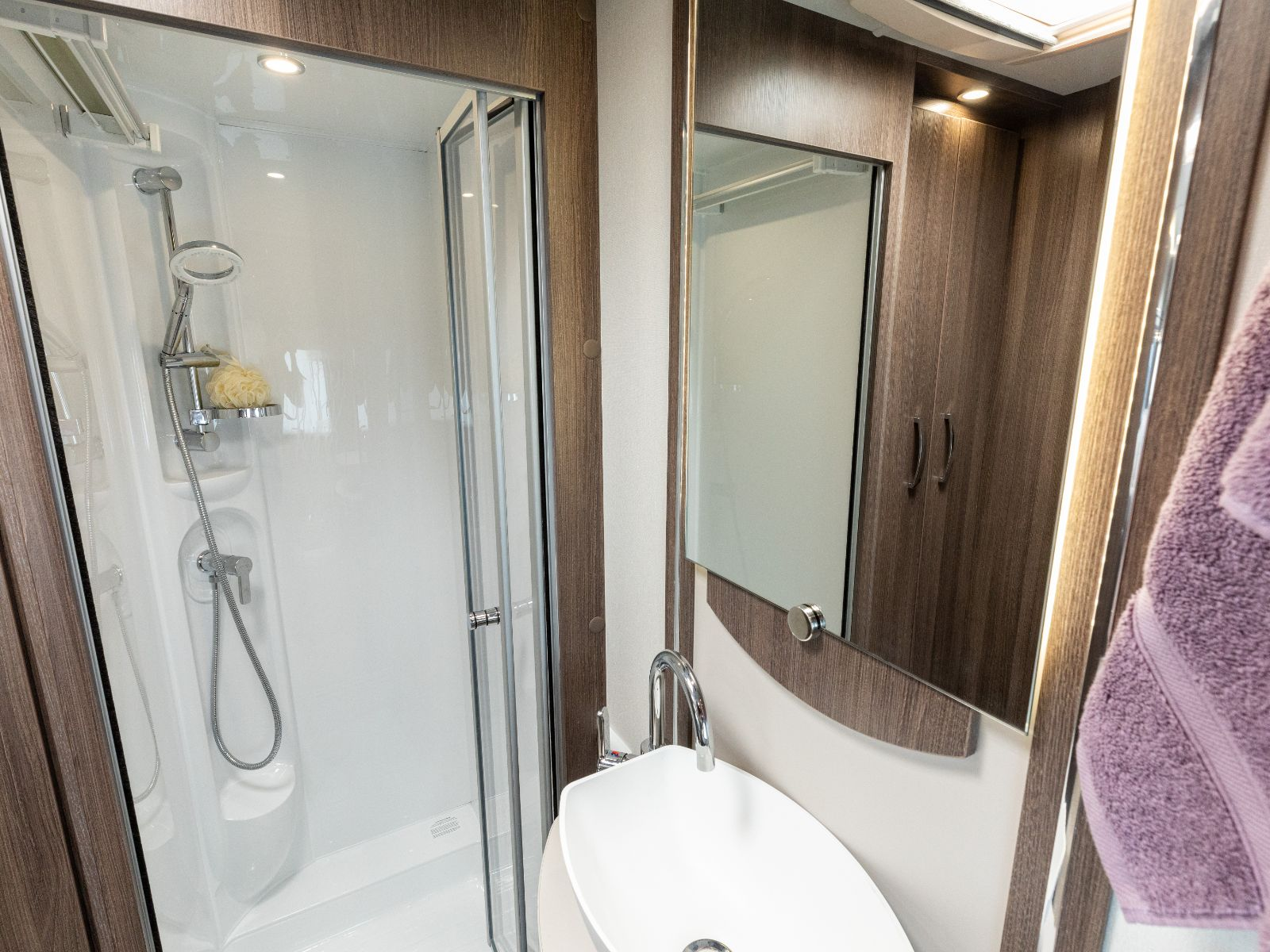 Bathroom layout with sink with mirror above and shower in corner of room'