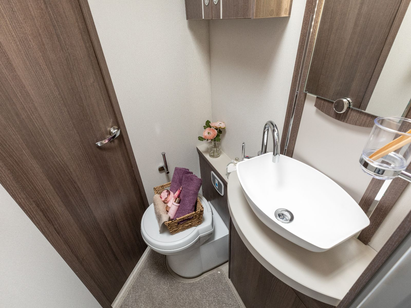 Bathroom layout with sink and toilet with toiletries on top'