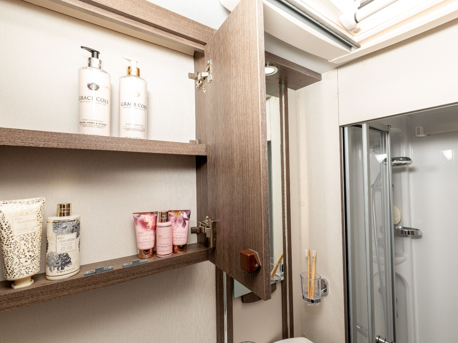 Toiletry storage cupboard with shower in background'