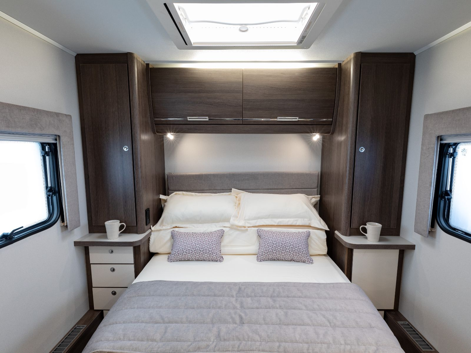 Bedroom layout with double bed and overhead storage'