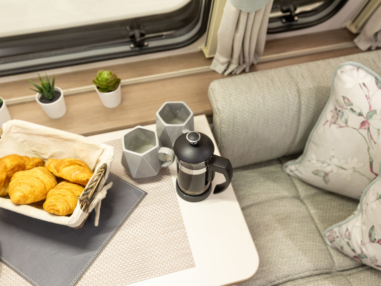 Lounge side table with coffee, cups and assortment of pastries'