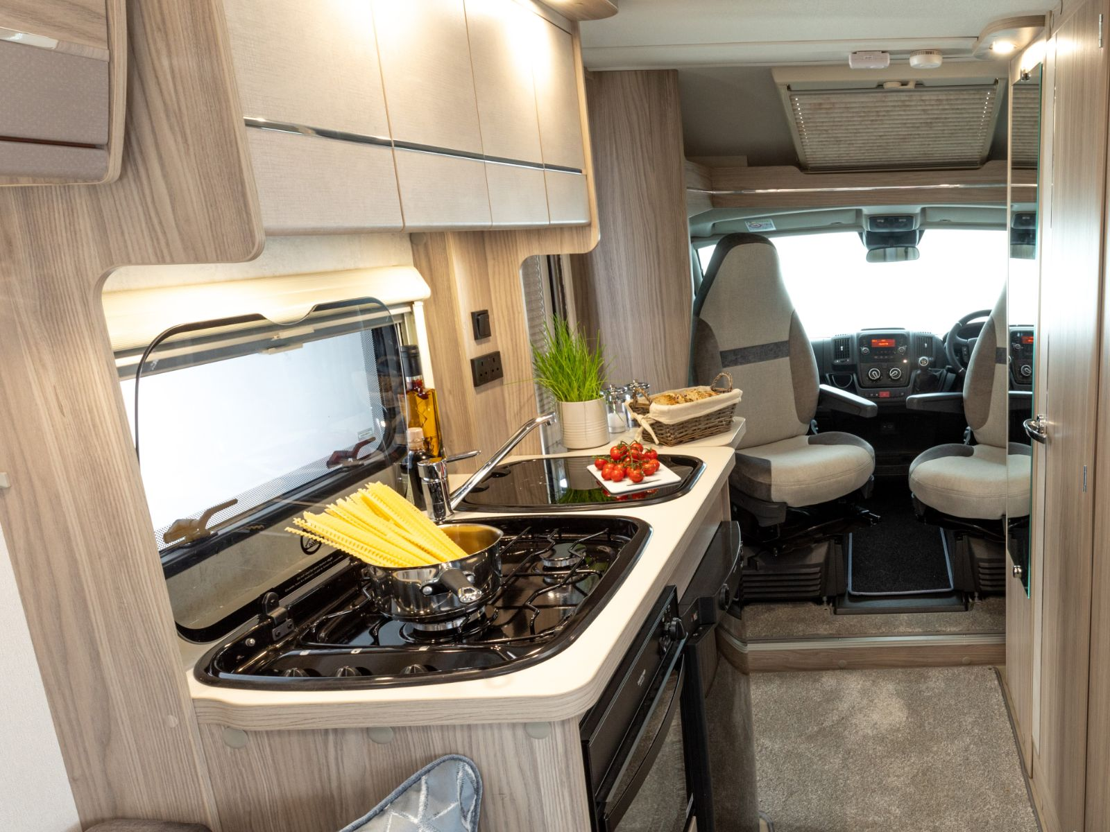 Kitchen layout with overhead storage and bread resting on the stove top with a view of the passenger seat'