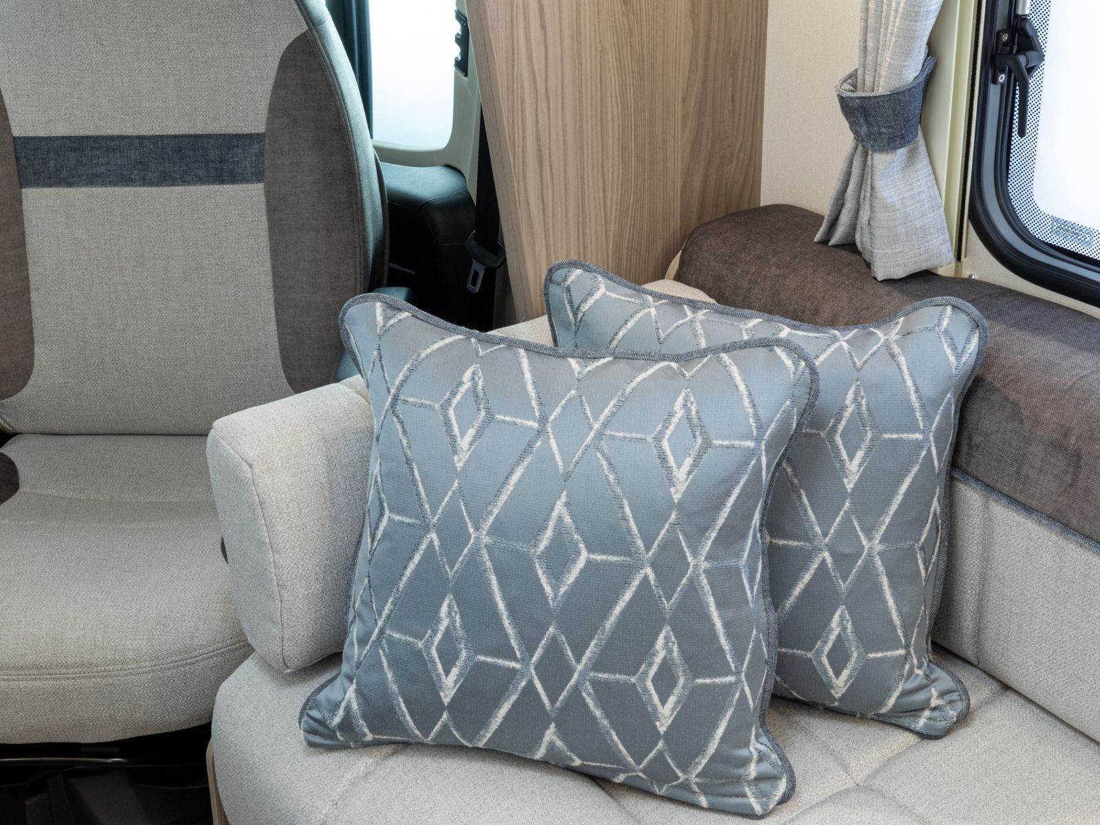 Sofa decorated with cushions and the drivers seat behind it'