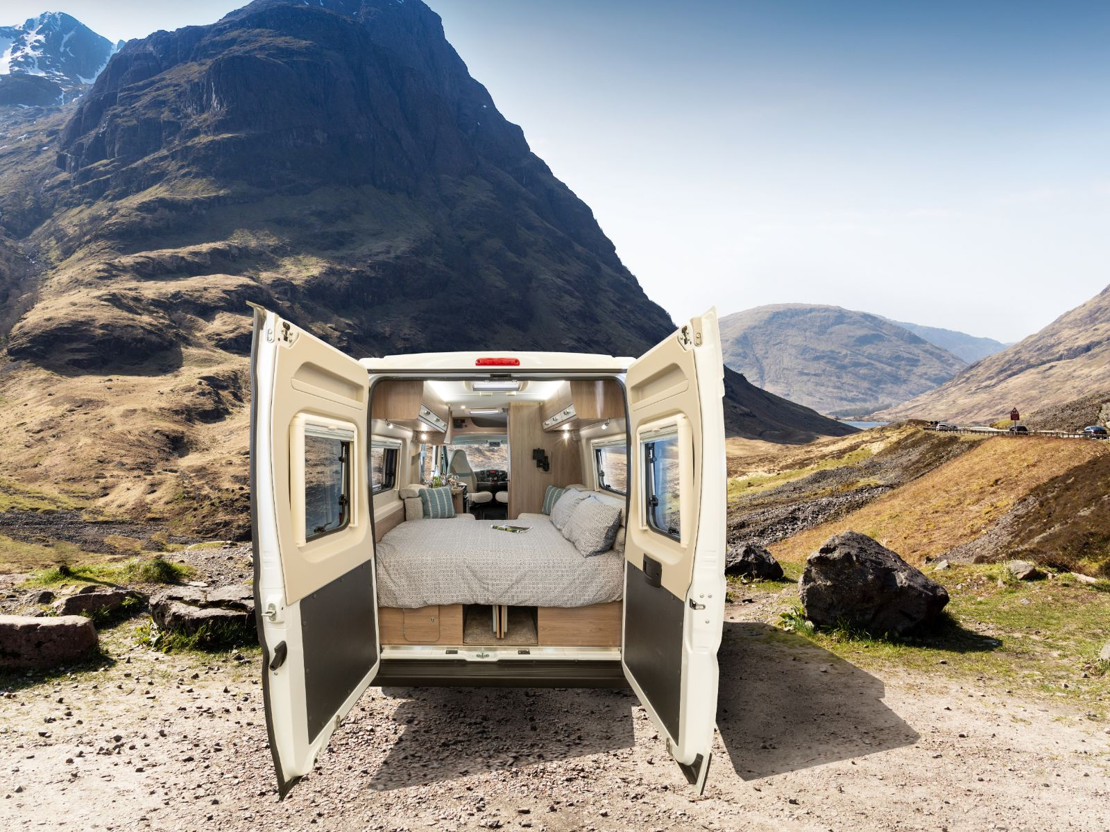 Rear view of the Avantgarde CV20 with backdoors open revealing the bedroom layout with a mountain view backdrop'