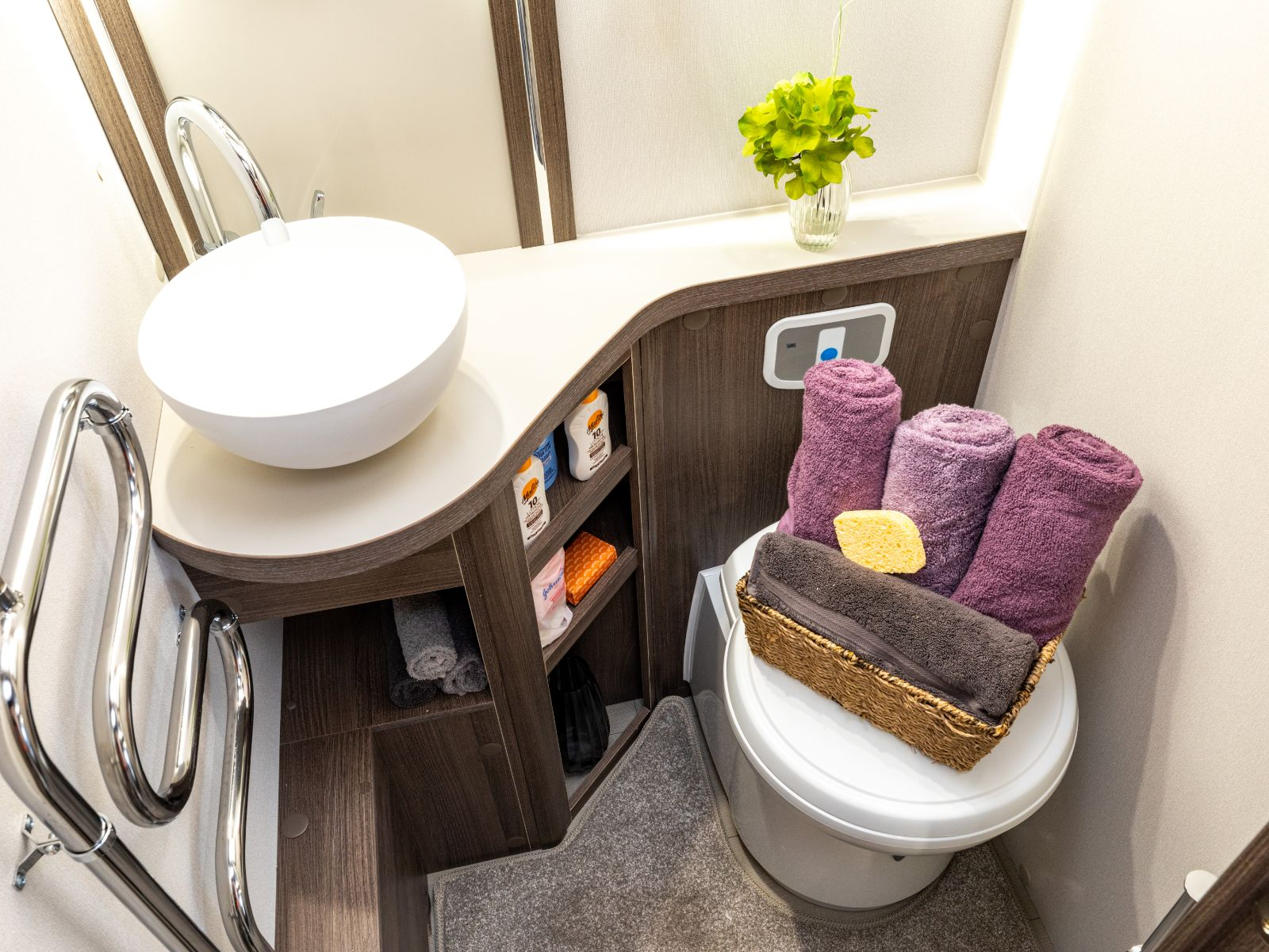 Toilet and sink with basket of towels on top of toilet and storage with toiletries '