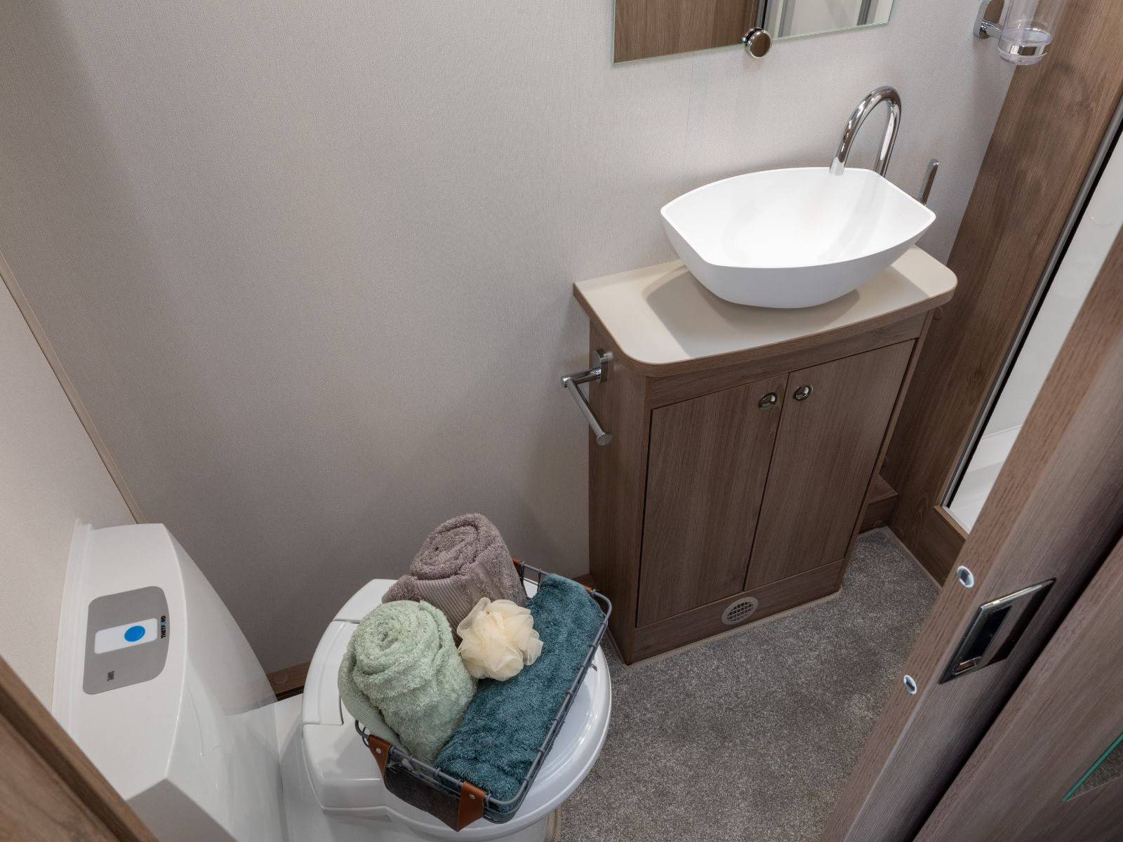 spacious bathroom with toilet and sink unit with storage '