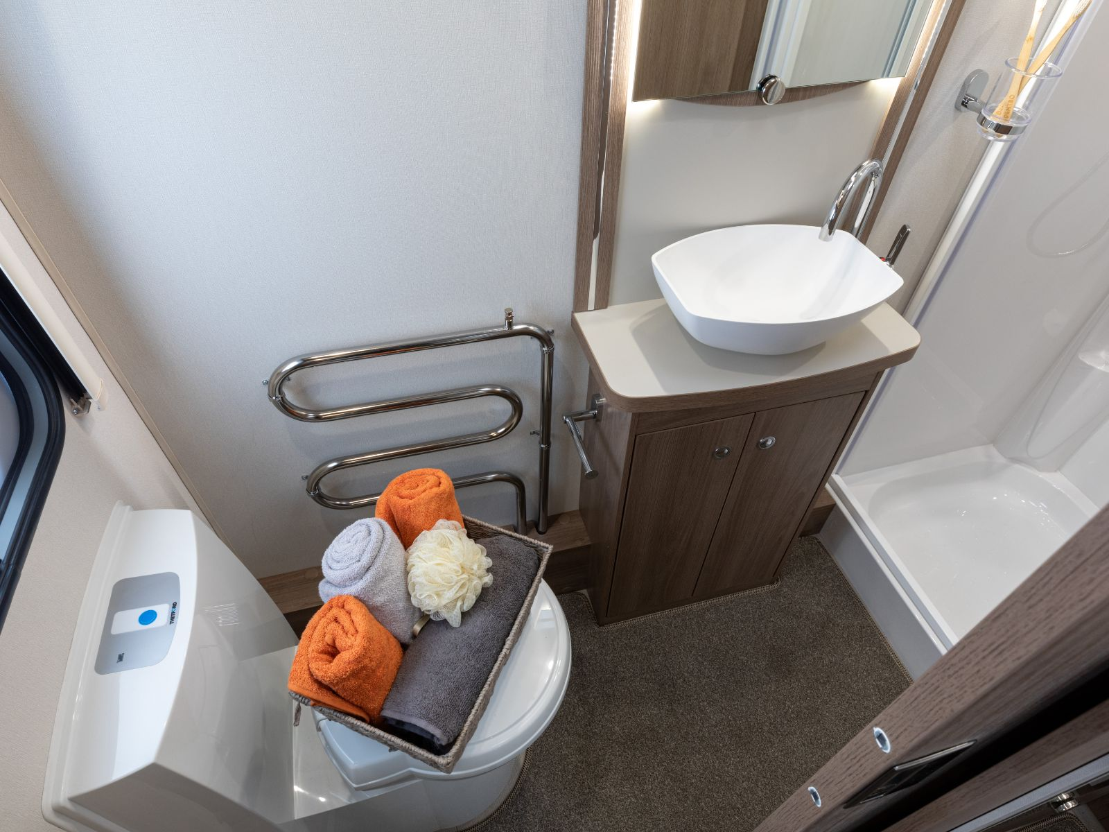 bathroom with sink and toilet with basket of towels on top '