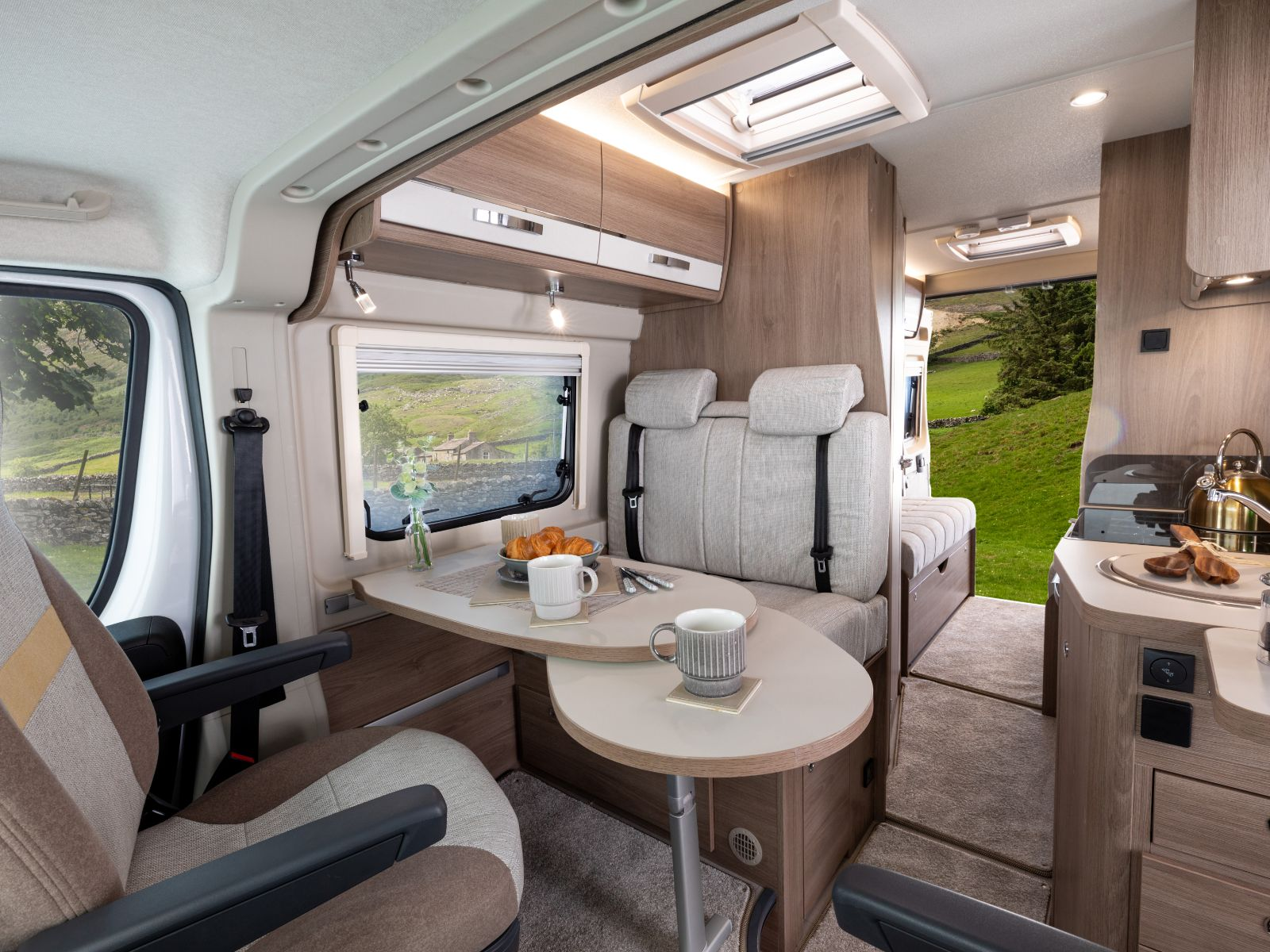 Passengers view of dining area and rear of the van with a forest backdrop '