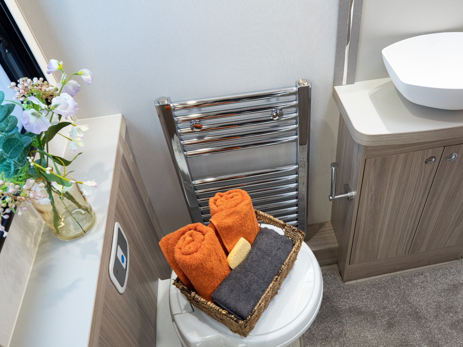 Toilet and sink with basket of towels on top of toilet and heated towel rail '