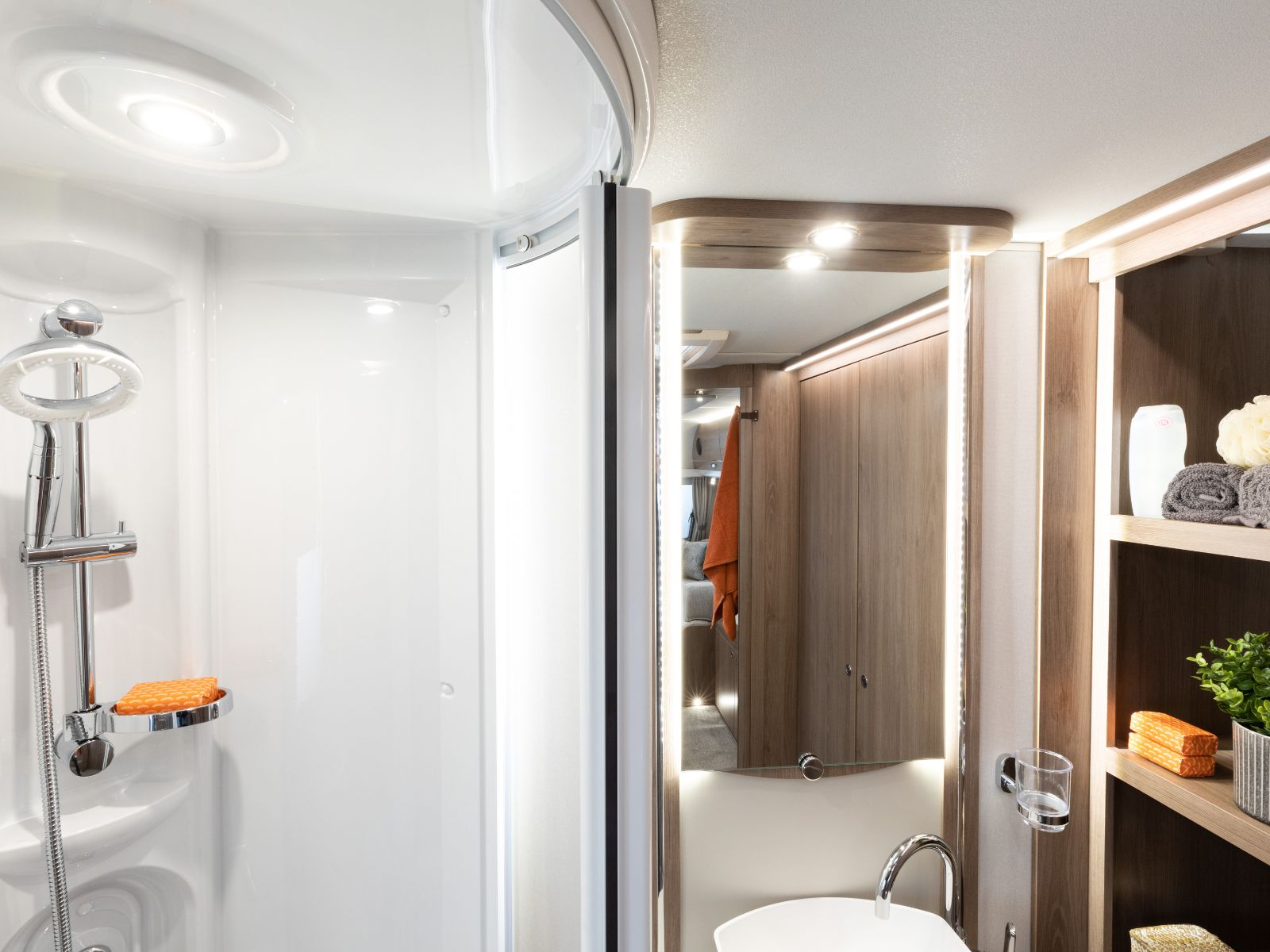 Large bathroom with shower, large back lit mirror and storage area '